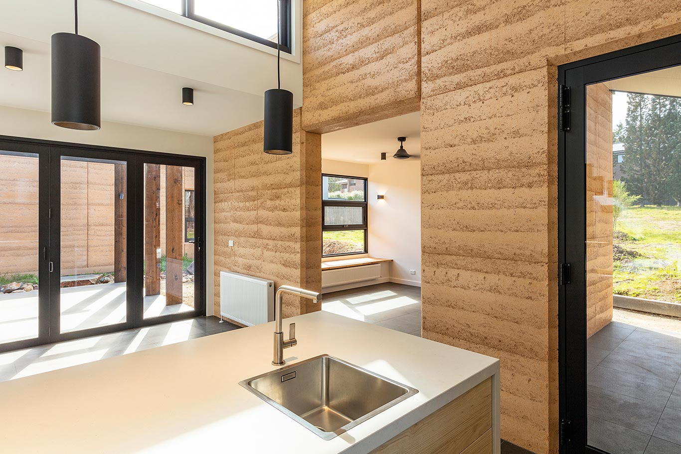 rammed earth home bright kitchen